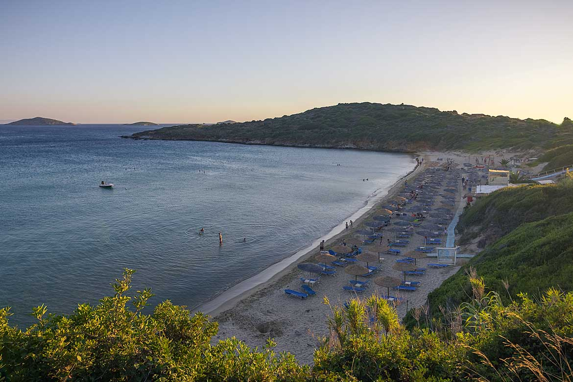 This is a panoramic shot of Chryssi Ammos beach at sunset. There are three long rows of sunbeds and straw umbrellas but they are almost empty at this hour. The sea is absolutely calm and there are only a handful of people swimming.