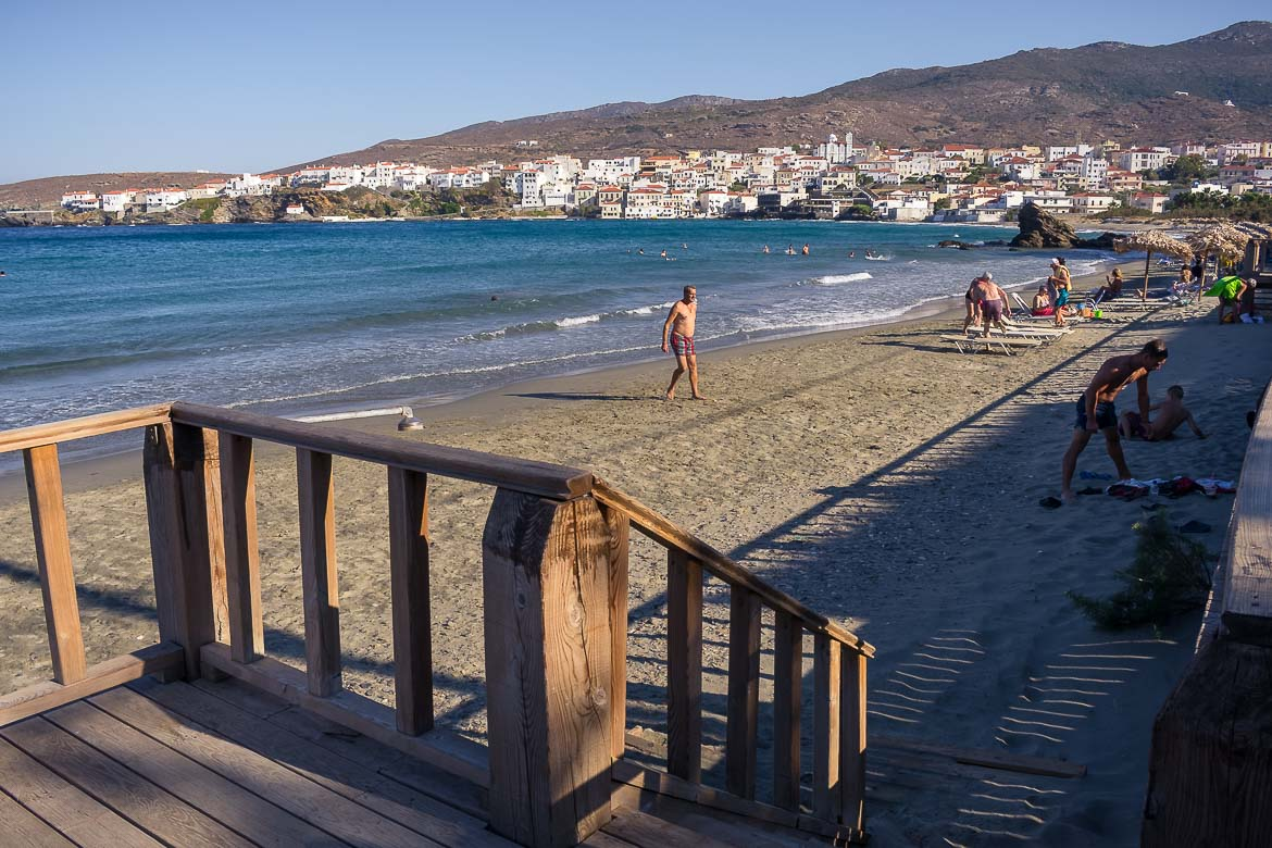 This image shows Nimporio Beach. There are people of all ages on the beach. The water is shallow and this is why Nimporio is one of the best Andros beaches for families.