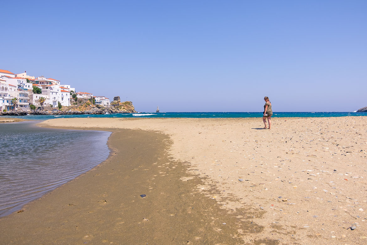 This is an image of Maria walking on the sand at Paraporti Beach. In the background, the gorgeous neoclassical mansion of Chora (Andros Town).
