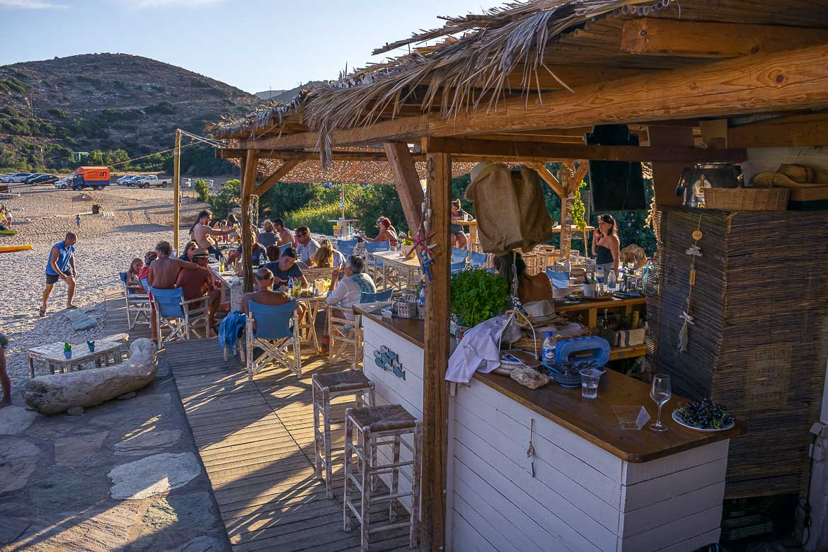This photo shows the seating area of the beach bar at Vitali. There are many people sitting there eating or drinking under the straw roof.