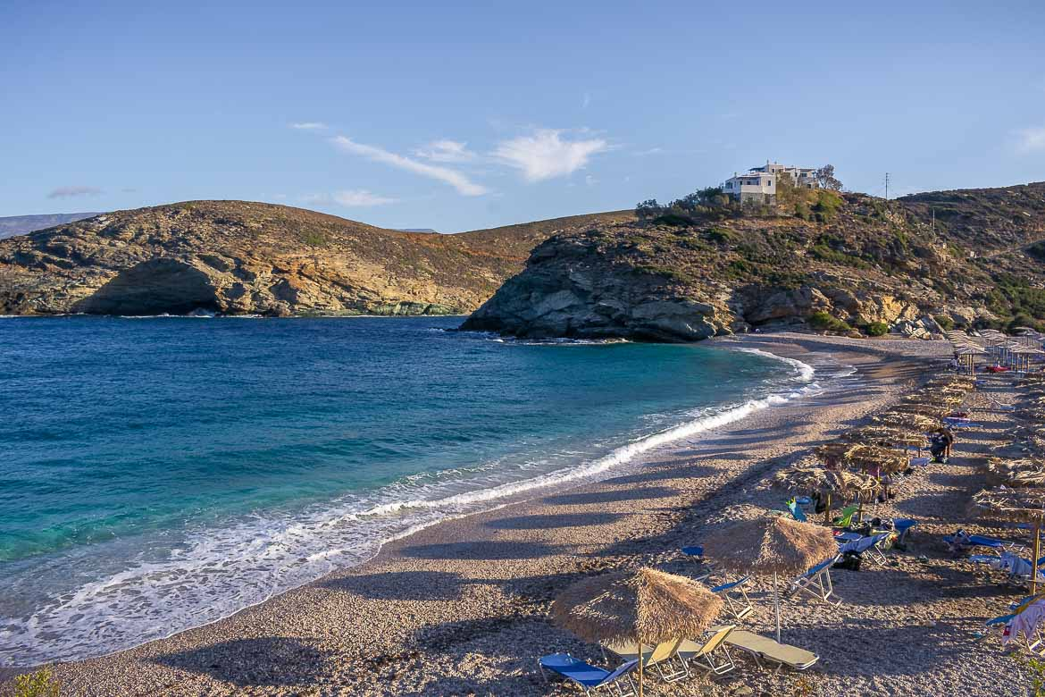 This is an image of Vitali Beach. There are sunbeds and straw umbrellas on the sand. The sea is a wonderful blue colour.