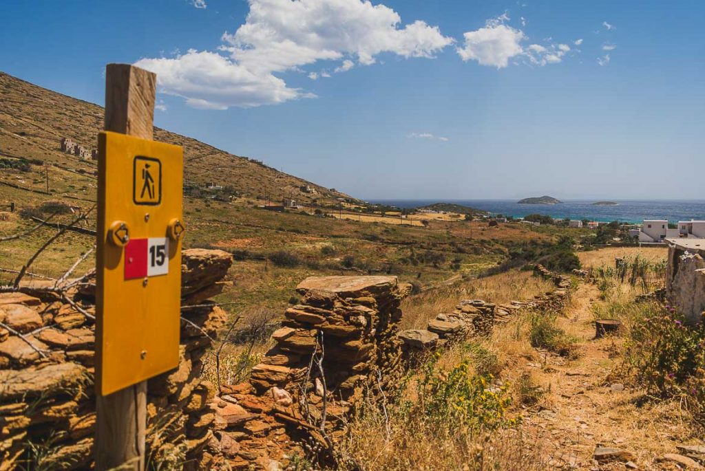 This picture shows a signpost of route 15 with the sea in the background. Andros hiking means walking along paths of unique natural beauty.