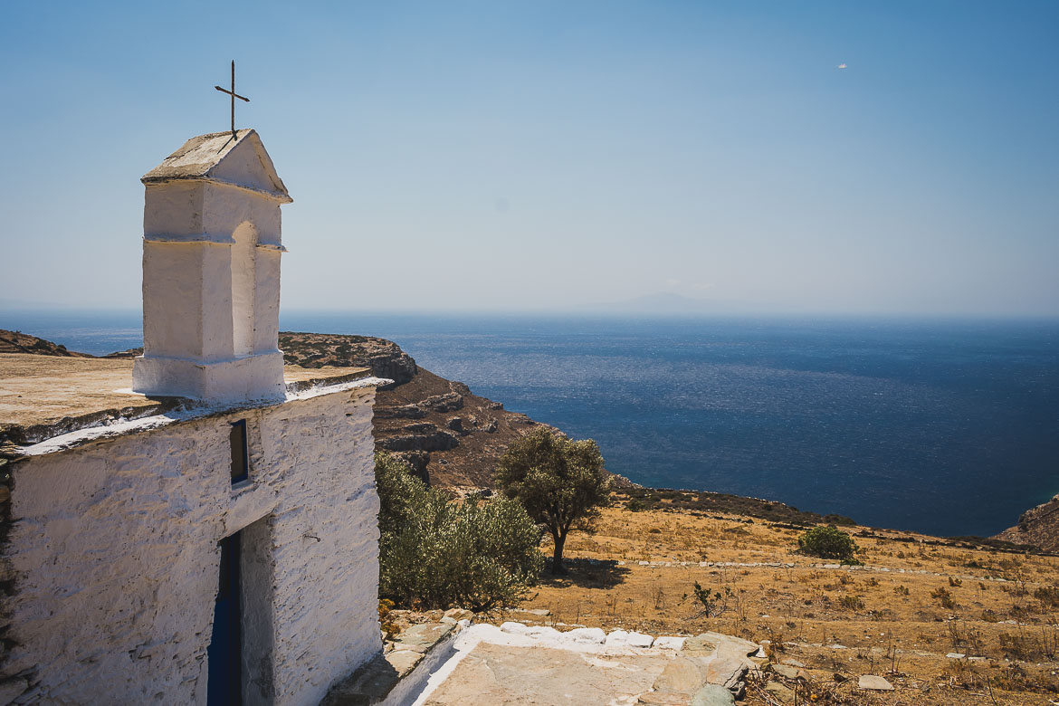 This photo shows a tiny whitewashed church perched on a hill overlooking the deep blue sea. Andros Routes offer everyone the opportunity to hike on one of the most beautiful Greek islands, Andros in the Cyclades, Greece.