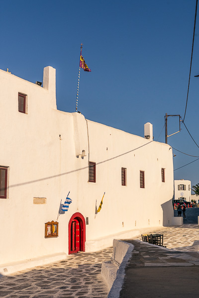 This is an image of the Monastery of Panagia Tourliani in Ano Mera. It is an all-white building with a red door.
