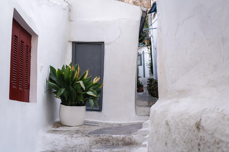 This image shows a a quaint white street in Anafiotika neighbourhood in Plaka.