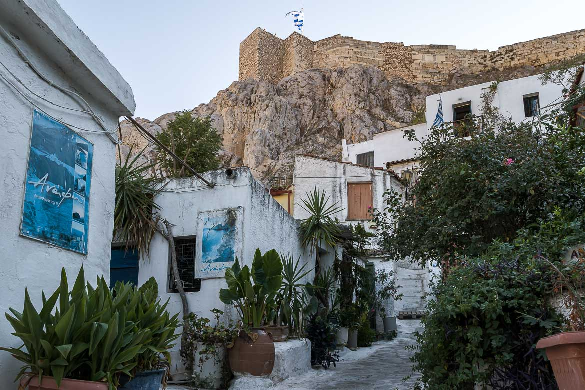 This image shows Anafiotika neighborhood in Plaka. There are whitewashed buildings under the shade of the Acropolis. A stroll around Anafiotika is a must during your Athens in 3 days itinerary.