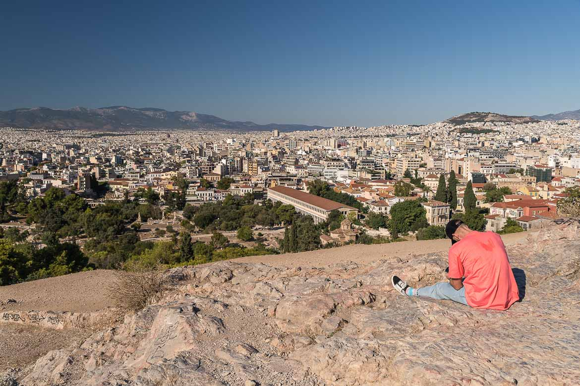 This image shows the view to Plaka from Areopagus Hill. In the foreground, there is a man resting on the rocks.