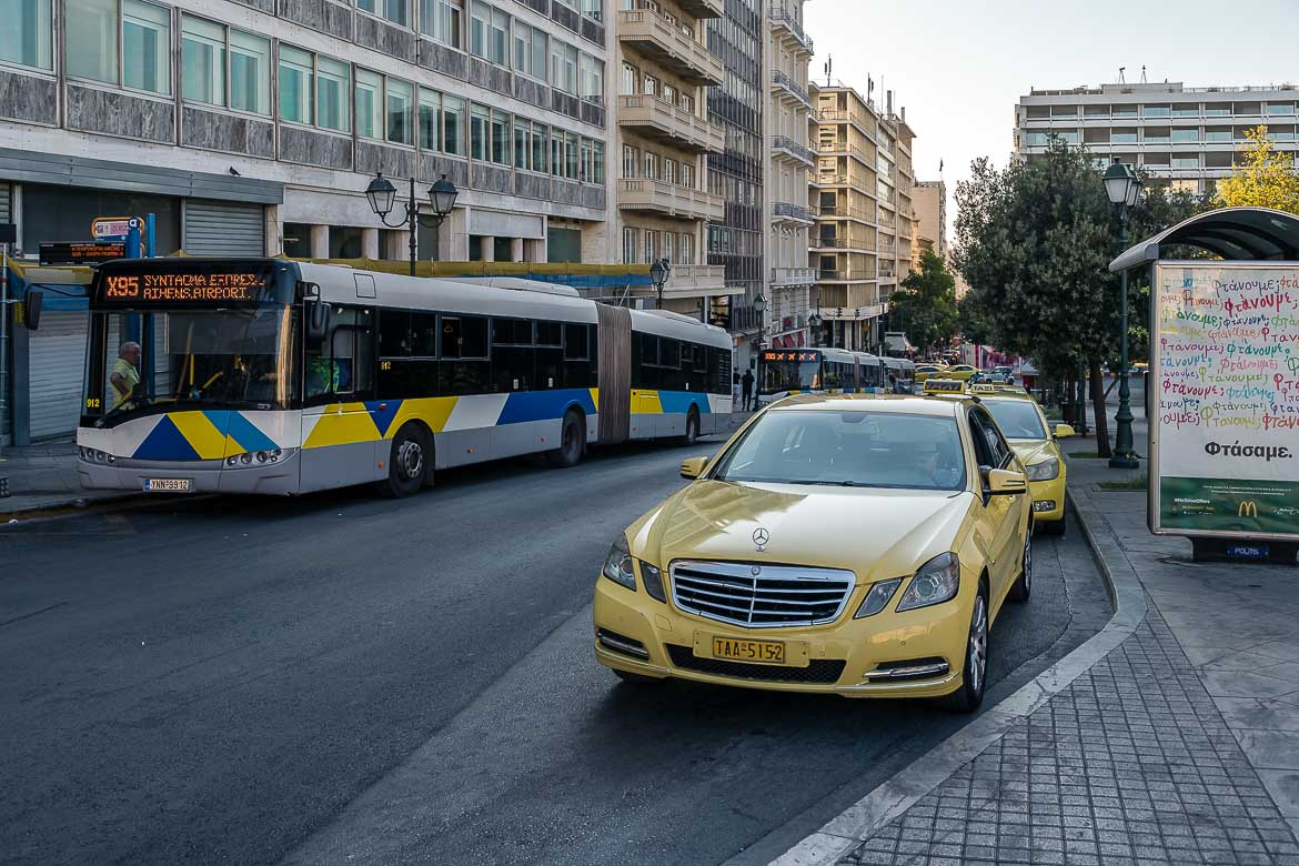 This image shows the X95 bus which goes to Athens airport and a line of taxis at Syntagma square.