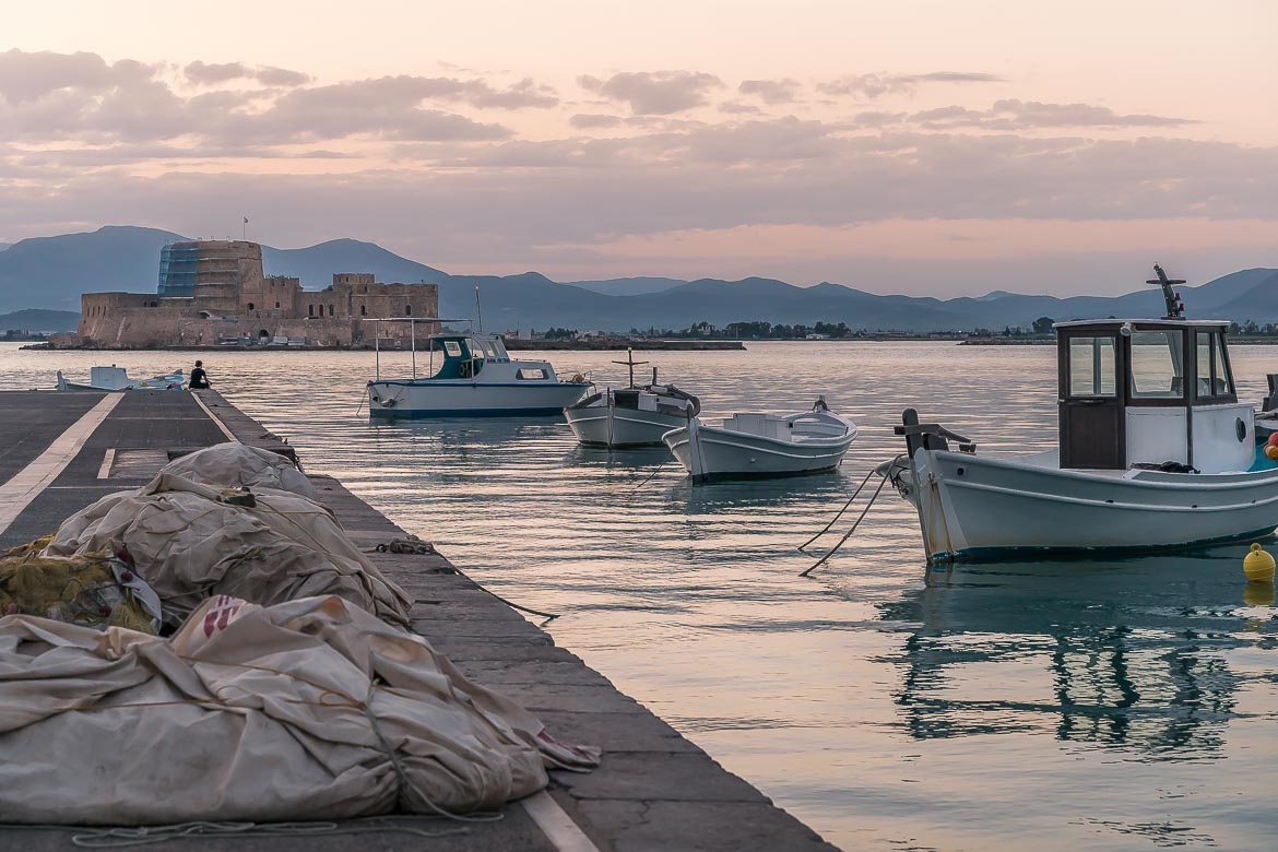 This image shows a few fishing boats near the quaint port in Nafplio. In the background, there is Bourtzi, a gorgeous fortress in the middle of the sea.