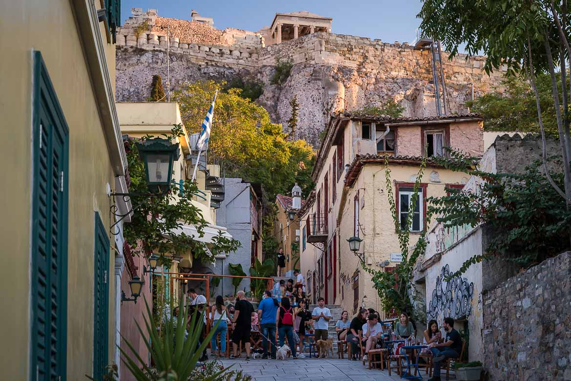 This image shows a quaint street in Plaka with beautiful cafes. In the background there is the Acropolis.