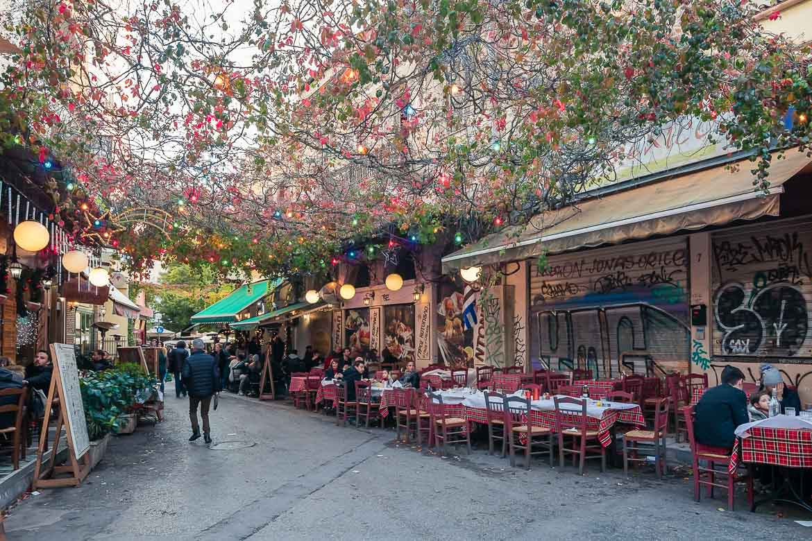 This image shows a street with tavernas in Psirri neighbourhood. There are Christmas lights but people still sit outdoors.