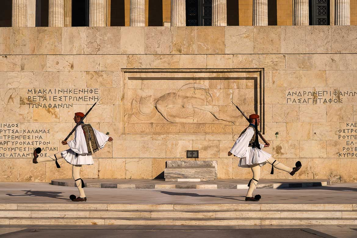 This image shows the change of the Presidential Guard in front of the Tomb of the Unknown Soldier and the Greek Parliament building in Syntagma Square.