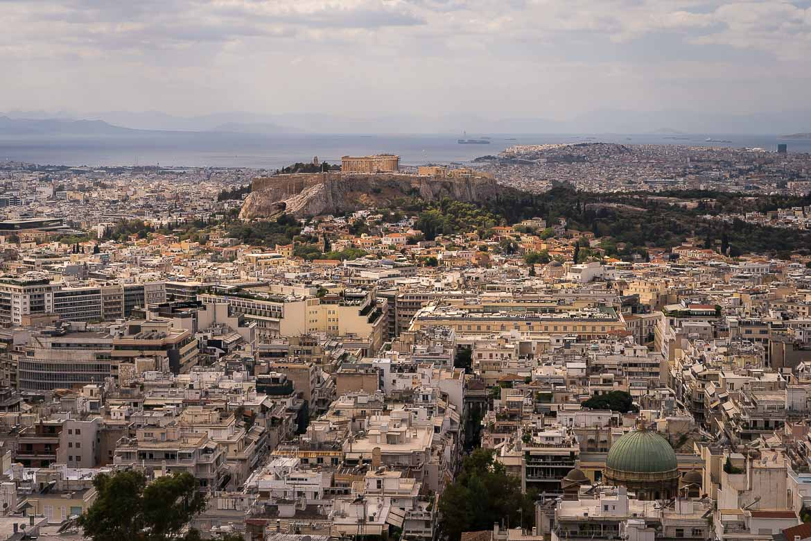 This image shows the view of Athens from Lycabettus Hill. We can see the Acropolis and the sea in the far background.
