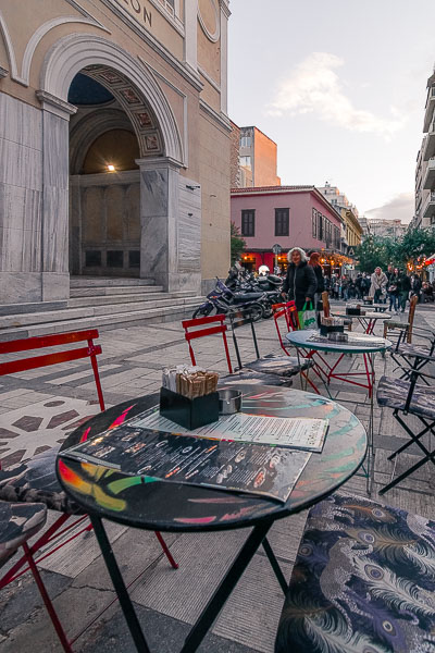 This image shows a cafe at Aiolou street. In the background, we can see Agia Irini church.