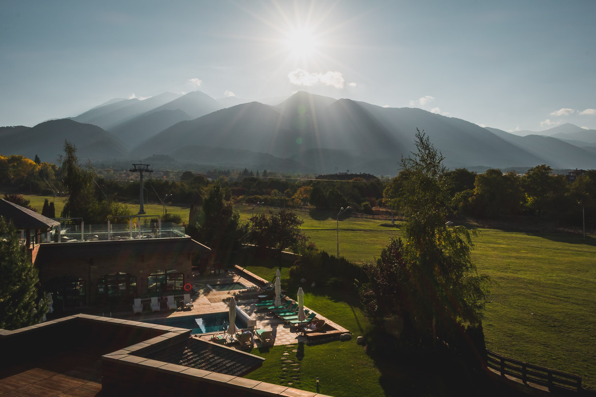 This photo shows the outside swimming pool of Kempinski Hotel Grand Arena Bansko Bulgaria with the mountains in the background.