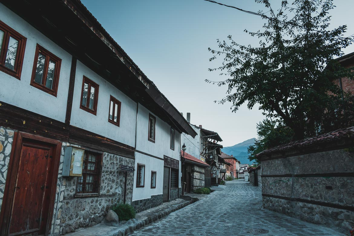 This photo shows a narrow cobbled street in Bansko Old town Bulgaria. There are traditional buildings lining both its sides.
