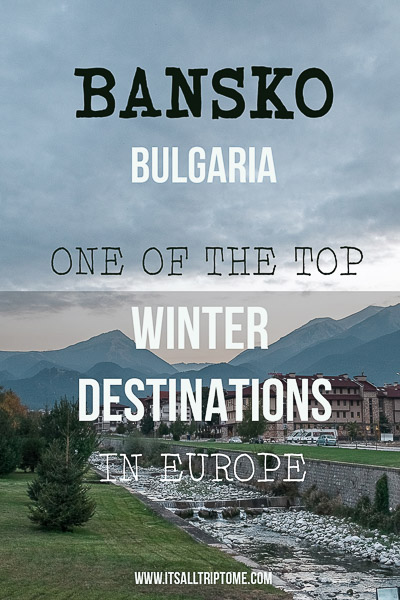 This image shows a river flowing through the mountain village of Bansko. In the background there are tall mountains. This is an optimised image for Pinterest. There is overlay text that reads Bansko Bulgaria, One of the top winter destinations in Europe. If you like our article about the top things to do in Bansko, pin this image!
