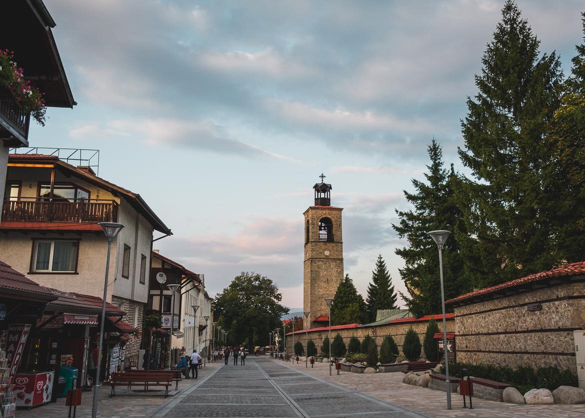 This photo shows Pirin Street, the main street in Bansko Bulgaria. There are people walking along the street. In the background, we can see the bell tower of Holy Trinity Church.