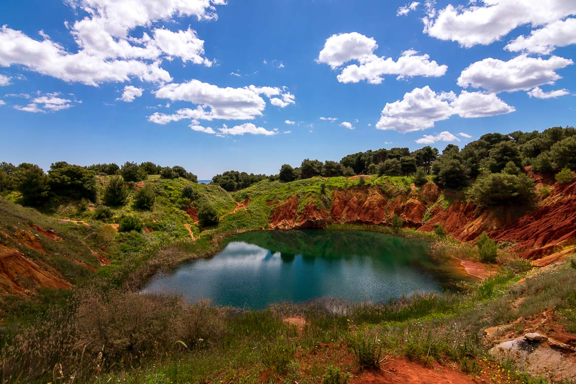 This is a photo of the bauxite lake. The lake's colour is green. It is surrounded by red rocks as well as trees. Above, a bright blue sky with only a few white clouds.