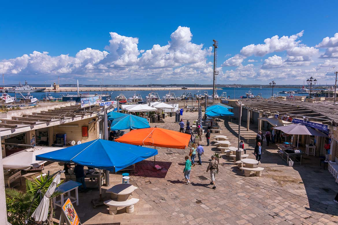 This is a photo of the fish market in Gallipoli. We can see various, empty now, stalls. There are large blue umbrellas and one orange. People are walking around the market.