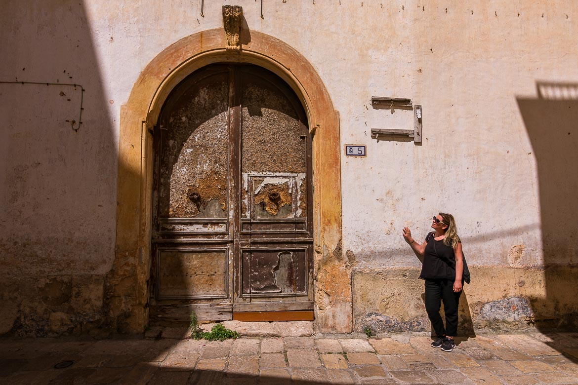 This is a photo of Maria standing by an old door. She is looking towards the door and smiling.