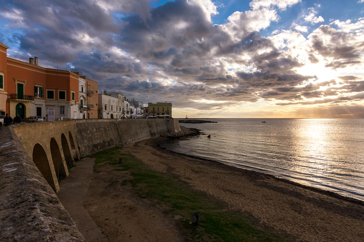 This photo shows the seafront promenade and the beach in Gallipoli at sunset. There is a cloudy dramatic sky as the sun dives into the Ionian Sea.