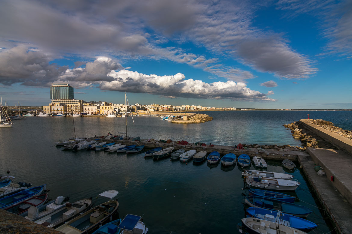 This is a photo of Gallipoli. In the foreground, the port in the Old Town with the small fishing boats. In the background, the modern part of the city. A tall ugly building stands above all the others under a beautiful afternoon sky.