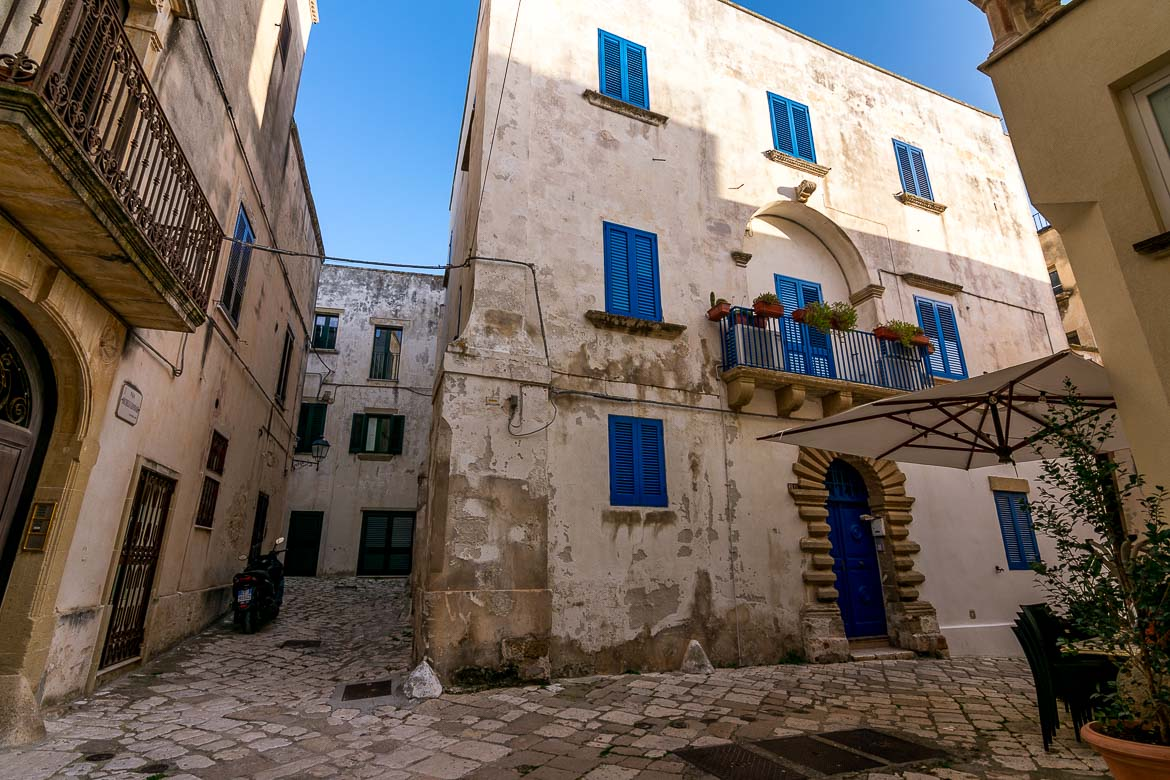 This is a photo of an old building in Otranto Old Town. It's a white 3-storey building with blue doors and windows.