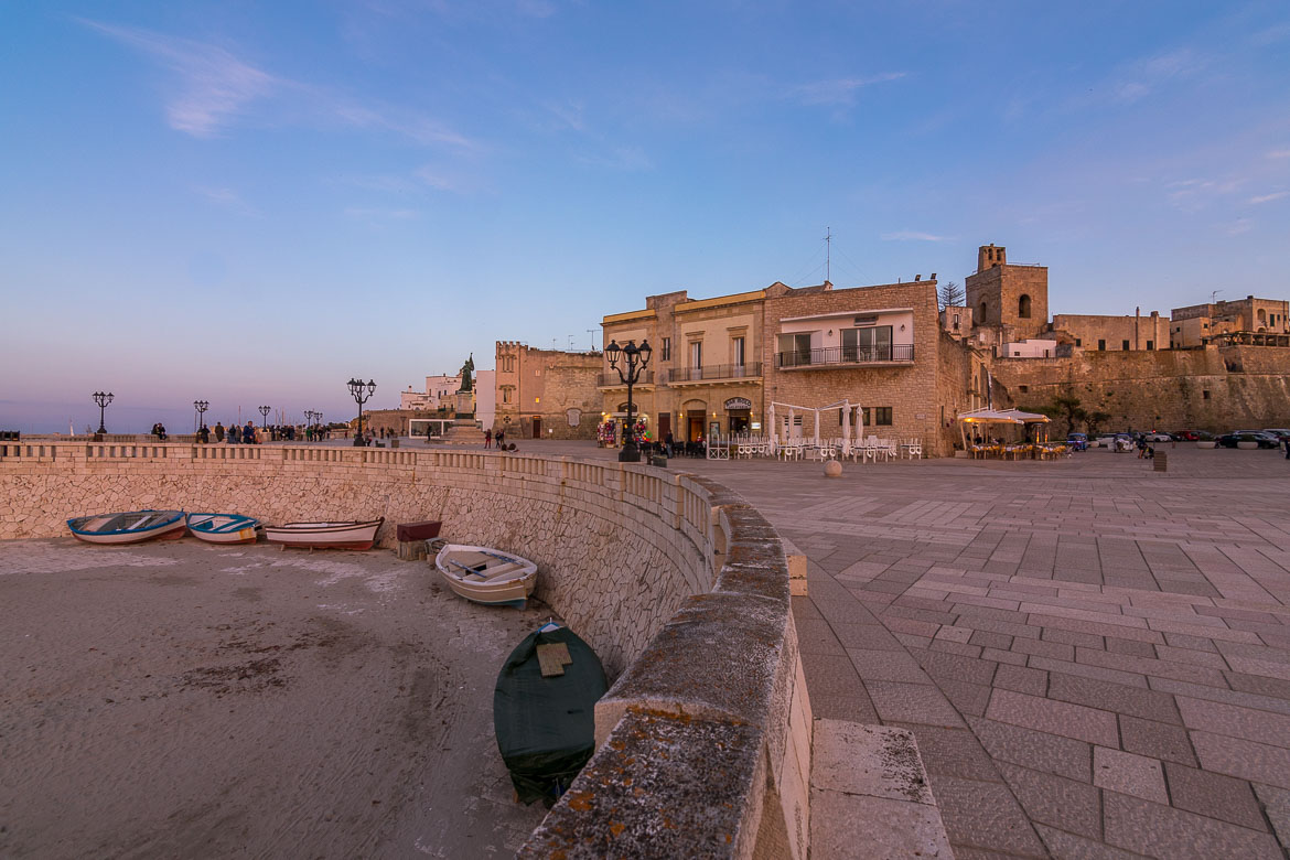 This photo shows the Heroes Promenade at sunset. There are charming palazzi along the promenade and boats on shore at the sand below the promenade.