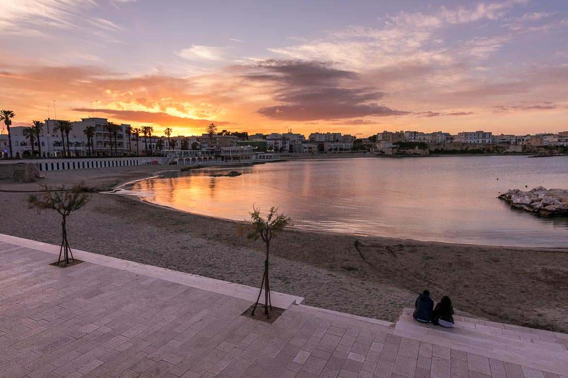 This is a photo of Otranto, one of the best beach towns in Puglia, at sunset. The sky is a dramatic blend of yellows, oranges, blues and purples which all reflect on the calm sea.