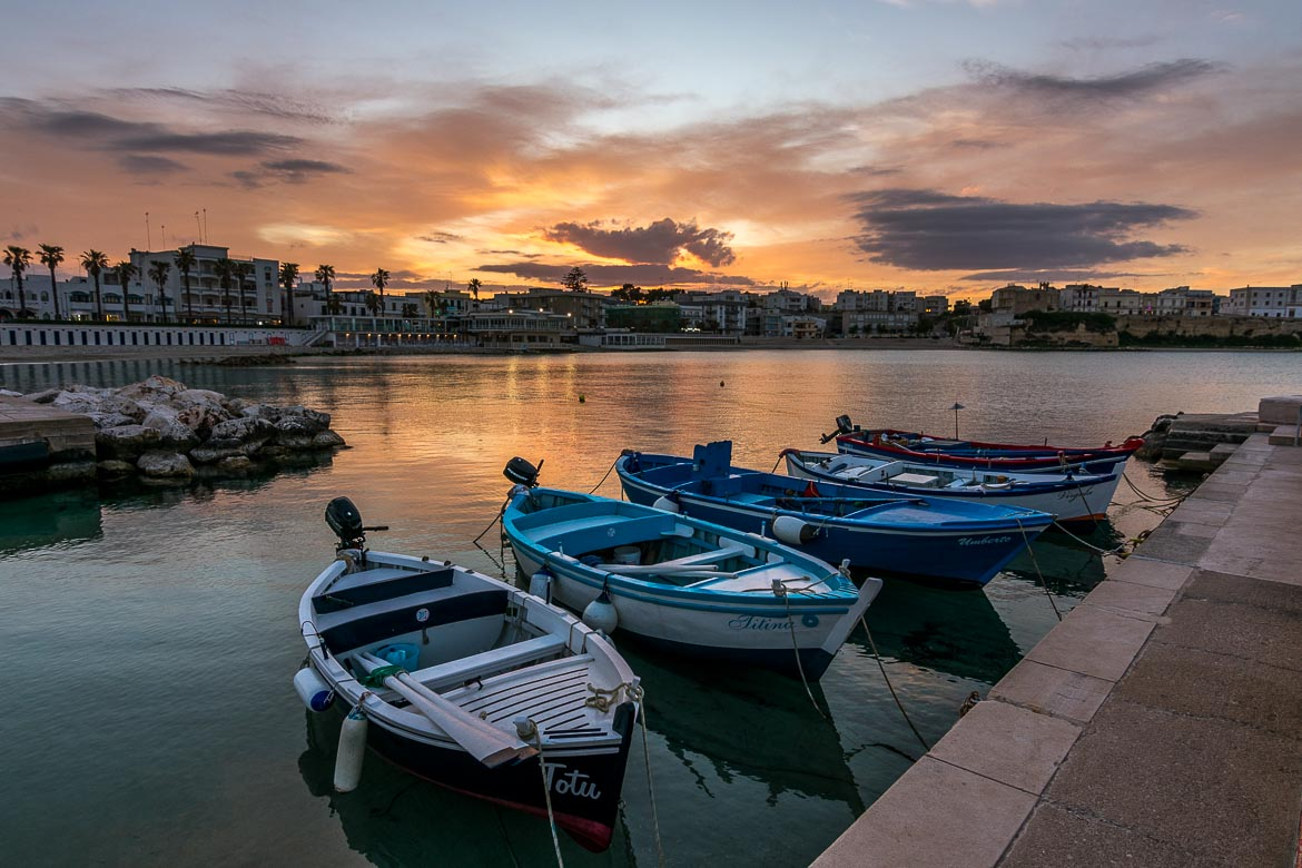 This is a photo of Otranto at sunset. In the foreground, a few small fishing boats in the tranquil sea. In the background, the dramatic sunset sky.