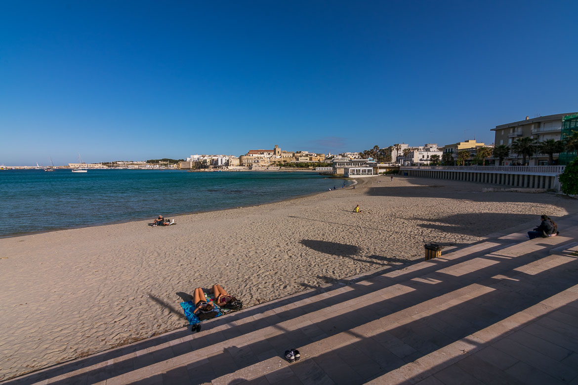 This is a photo of the long sandy beach in Otranto town. It has crystal clear waters and views to the old town. This is the main reason why we consider Otranto one of the best beach towns in Puglia Italy.