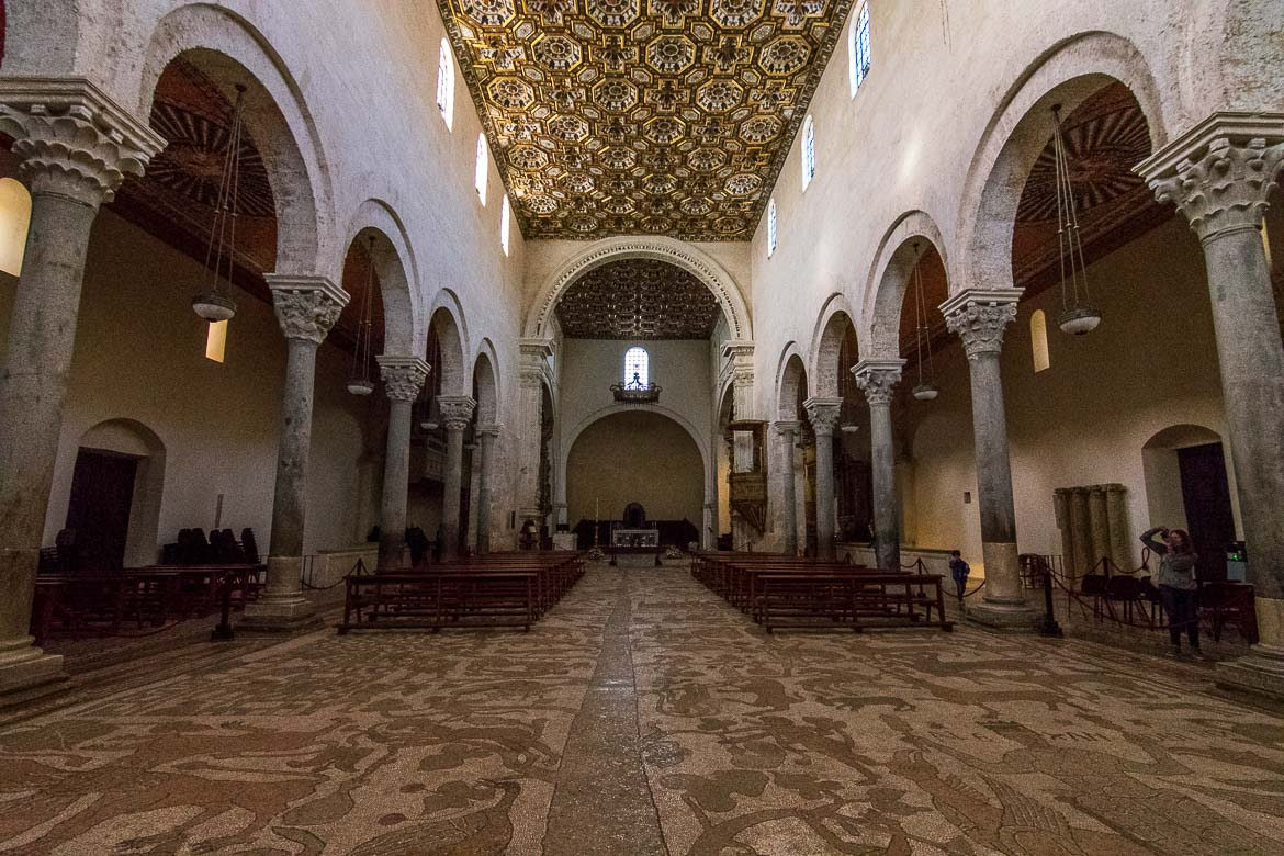 This photo was taken inside Otranto Cathedral. The focus is on the church's mosaic floor which depicts a huge Tree of Life. There are columns and arches on both sides of the church.