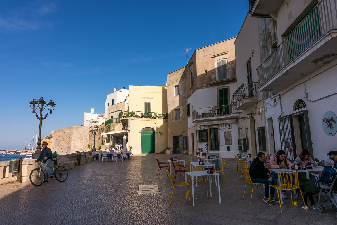 This photo shows the tables and chairs of Deja Vù Cafè on the Heroes Promenade. There are some people sitting there and there is also a man riding his bicycle past the cafe.
