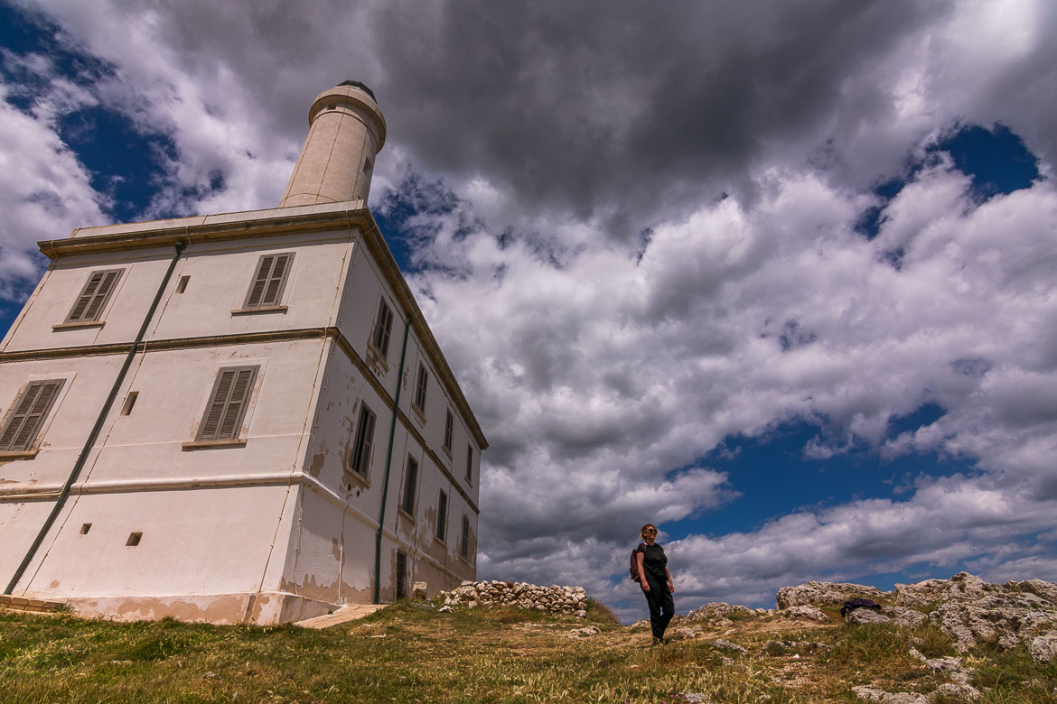 This photo shows the Punta Palascia Lighthouse. Maria is walking in front of it with a wide smile on her face.