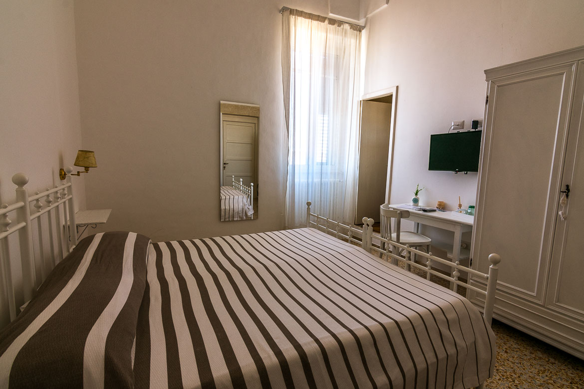 This photo shows our room at Palazzo Marzo. There is an iron bed covered with a striped throw, a white closet and a white desk. The room is very very bright.
