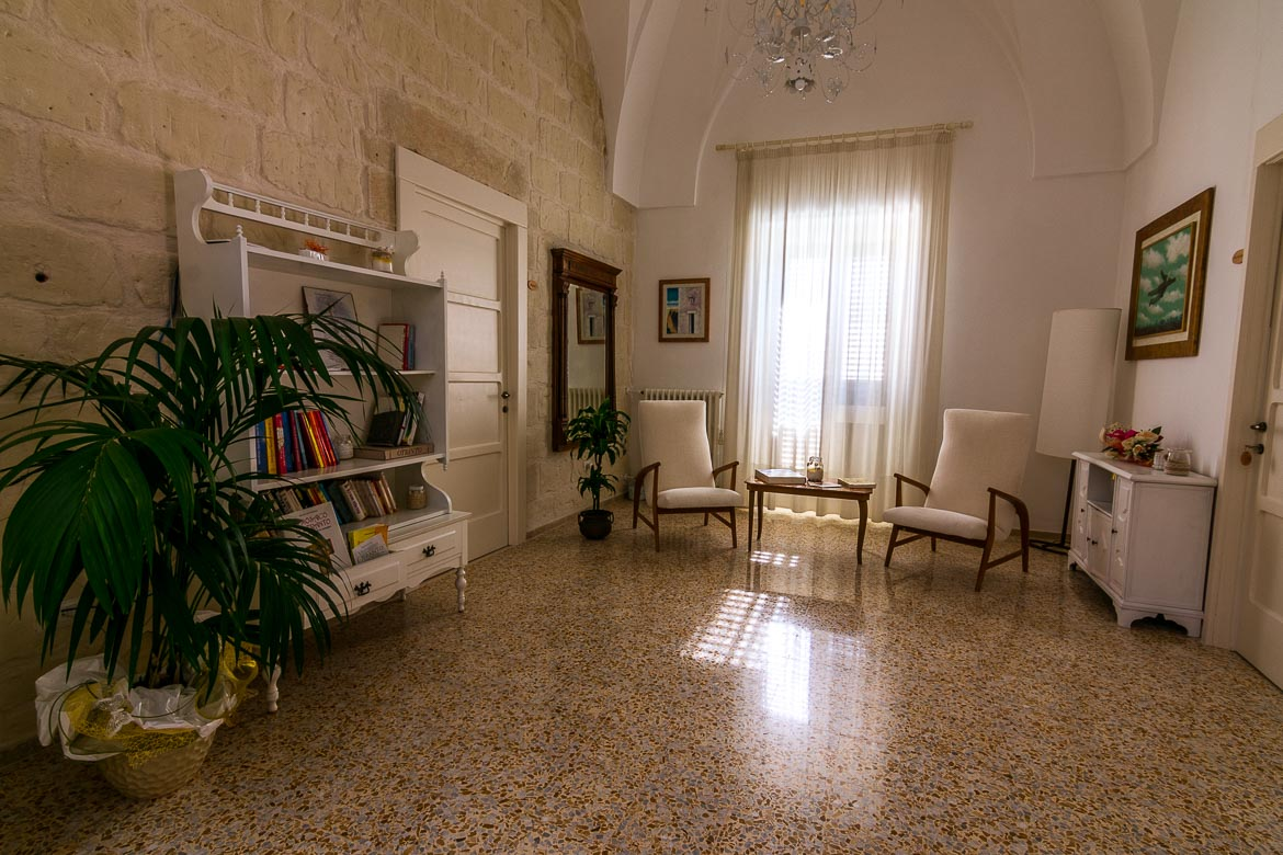 This image shows a sitting room in Palazzo Marzo. There are two white chairs, a coffee table, a white bookcase and white curtains on the french windows.