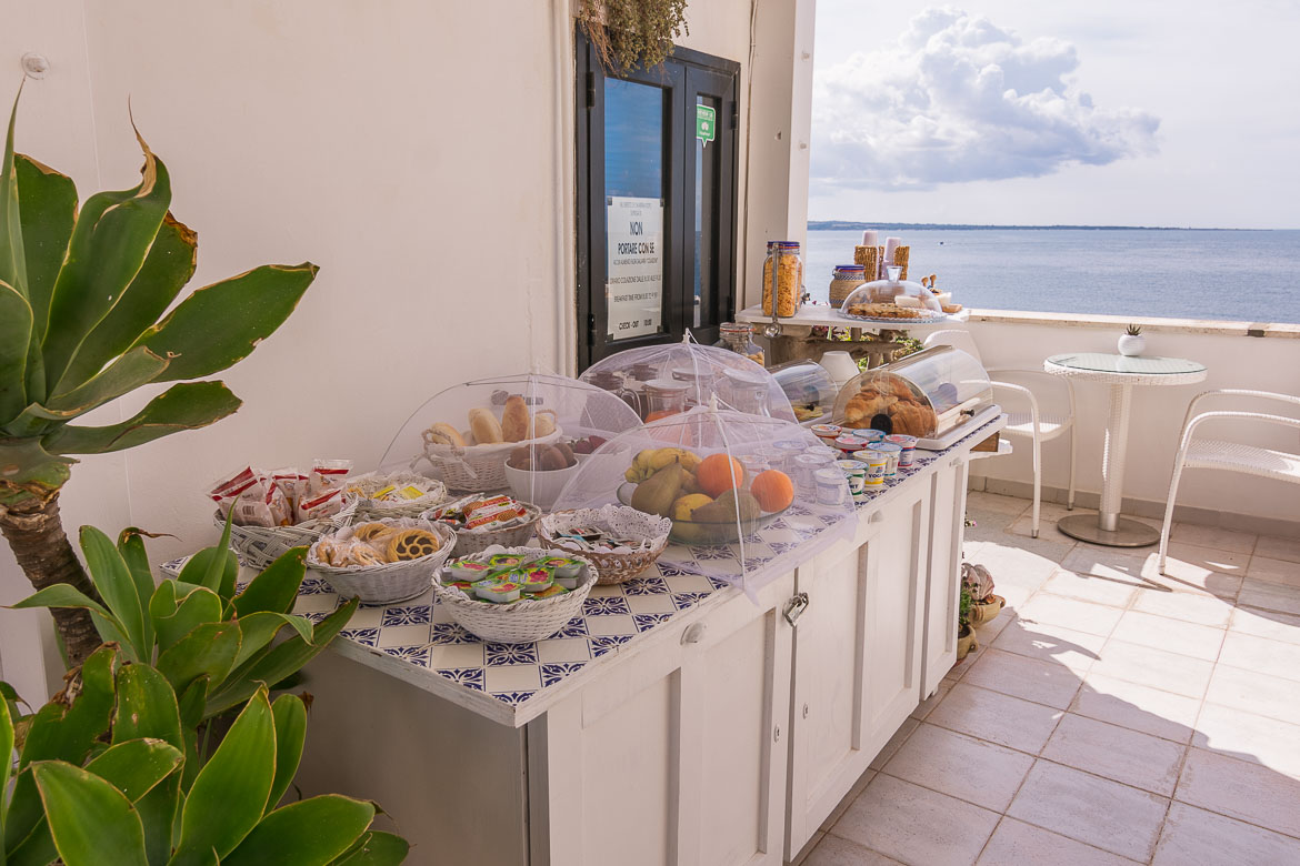 This photo shows the buffet breakfast at Punta Cutieri served at the B&B's terrace overlooking the Ionian sea. It is a sunny day and the sea is utterly calm.