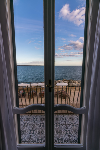This photo shows the view to the sea from inside the closed french windows in our room at Punta Cutieri.