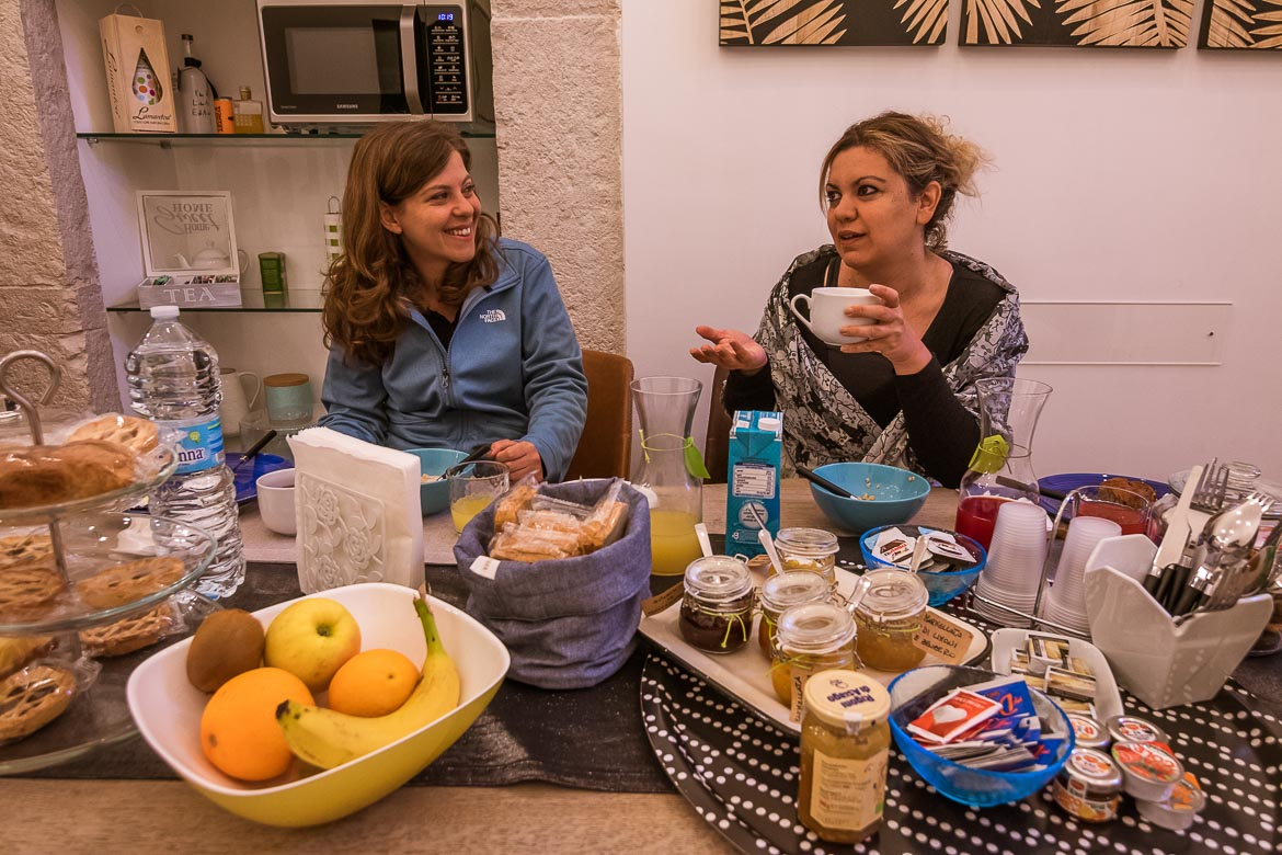 This photo shows Katerina and Maria having breakfast at Sotrani. They are chatting. Maria seems to be explaining something while Katerina smiles at her. There are jars of jam, fruit, coffee mugs and other treats in front of them.
