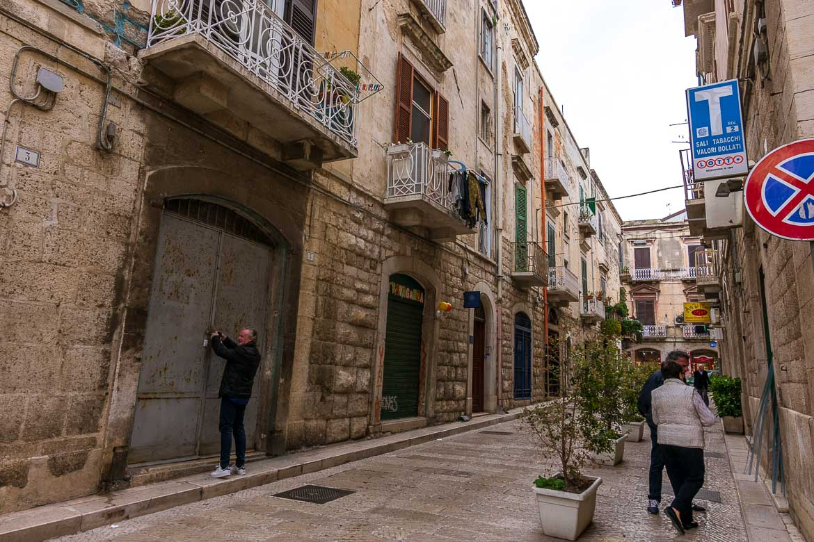 This photo shows a quaint street in Trani Old Town. The street is lined with beautiful palazzi and there are people coming ang going.