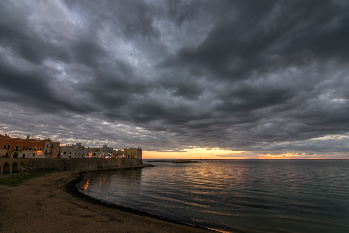 This is a panoramic shot of Gallipoli beach at sunset. The sky is stunning with grey clouds over the orange setting sun. To the left, the old palazzi of Gallipoli dimly lit look beautiful.