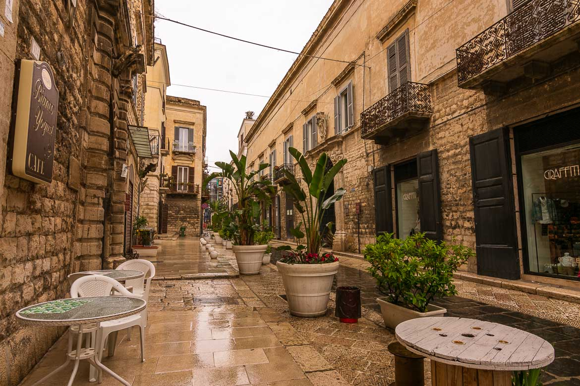 This is a photo of a narrow street in Trani Old Town. It is a rainy day, it's very cloudy and everything is wet: tables, chairs, flower pots. There is noone to be seen around.