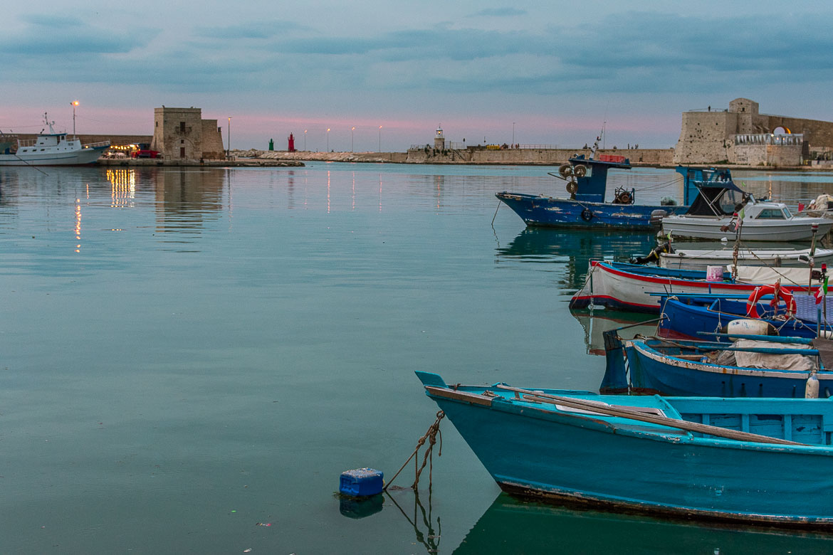 This is a photo of the port of Trani at sunset. The sea is calm. There are small blue fishing boats in the sea. The  sky is blue and pink.