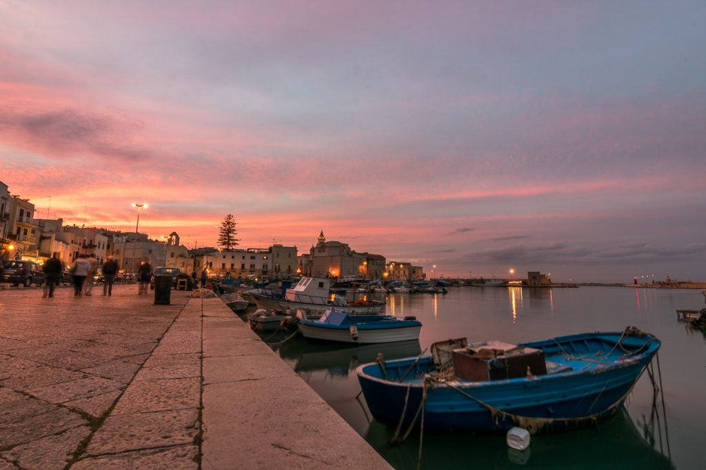 This image was shot in Trani port during sunset. The sky is a magnificent collection of pinks, yellows and blues, all reflecting on the mirror-like sea. There are small blue fishing boats in the sea and people walking along the promenade. The old-fashioned palazzi are dimly lit. We chose this photo to be the featured image for our article: Best beach towns in Puglia Italy for a laid-back vacation.
