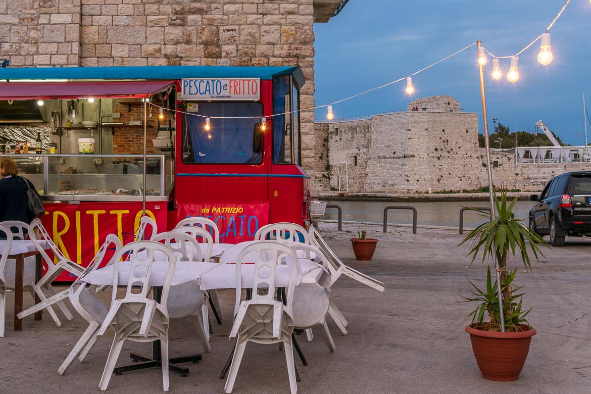 This photo shows a seafront food truck in Trani. The truck is bright red and it has Pescato e Fritto written on it. That loosely translates to freshly caught and fried. There are plastic chairs in front of the truck and a line of charming light bulbs above it.