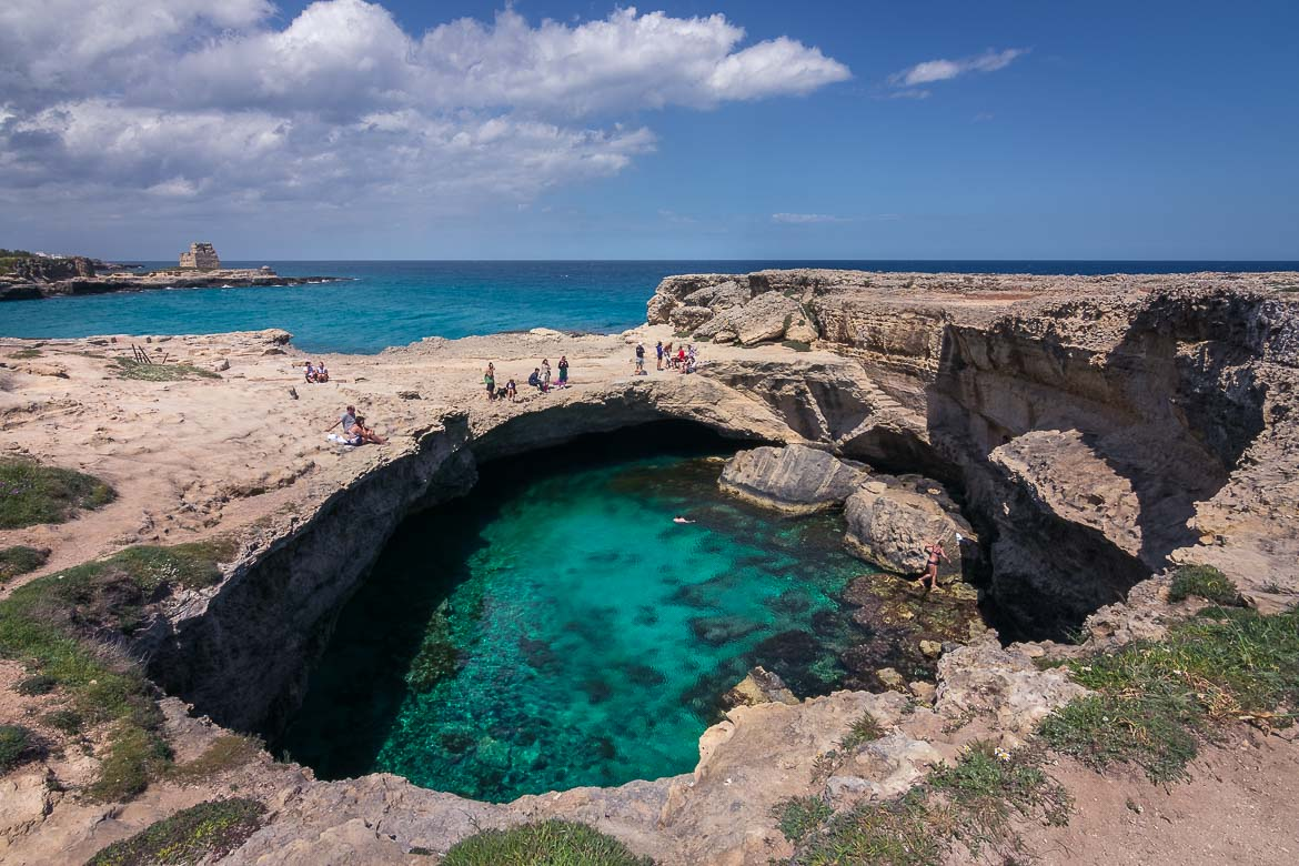 This is a panoramic shot of Grotta della Poesia. It is a natural pool surrounded by very tall cliffs from where some people are ready to dive in its emerald waters.