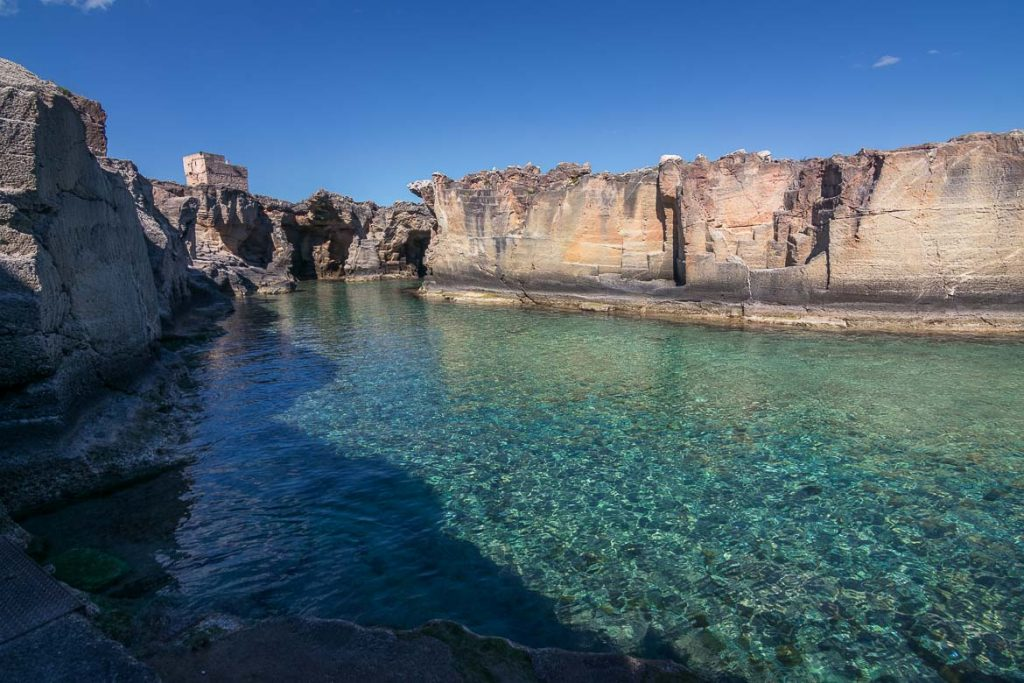 This is a photo of Marina Serra, a shallow natural pool with crystal clear waters surrounded by cliffs.