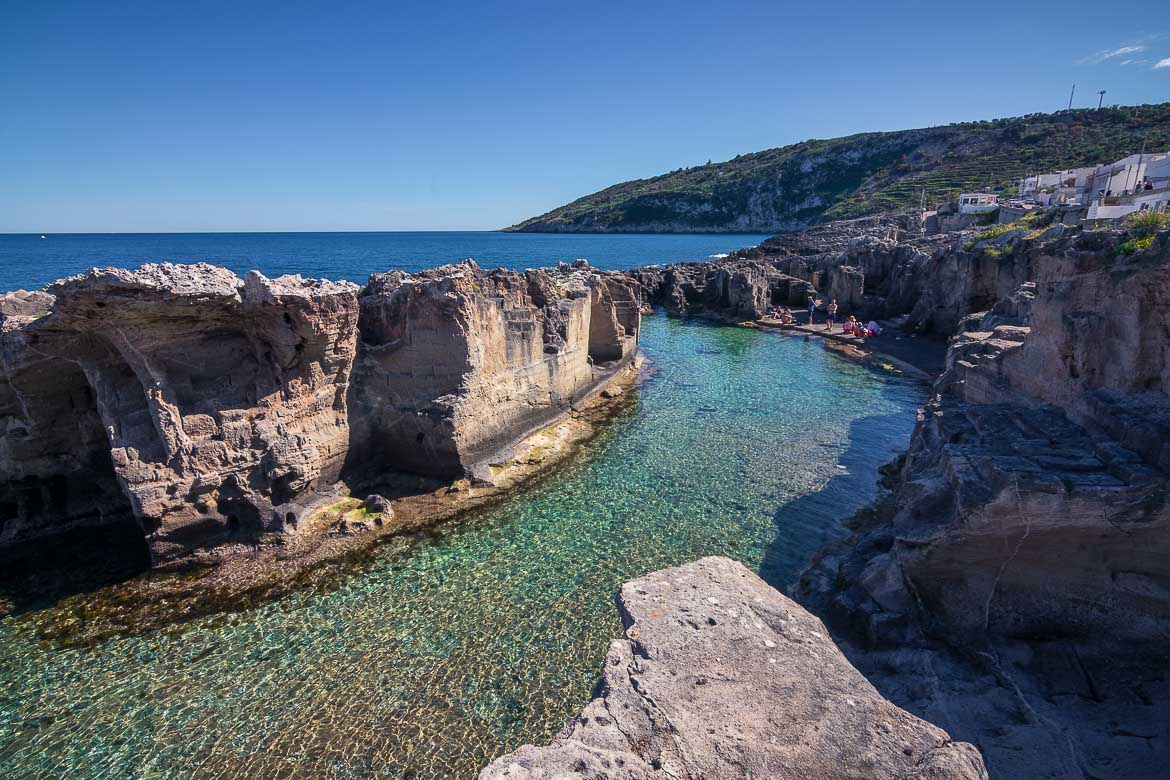 This is a photo of Marina Serra, a natural swimming pool of unique beauty. The waters are shallow and crystal clear. The pool is enclosed by cliffs, beyond which there is the open blue sea.
