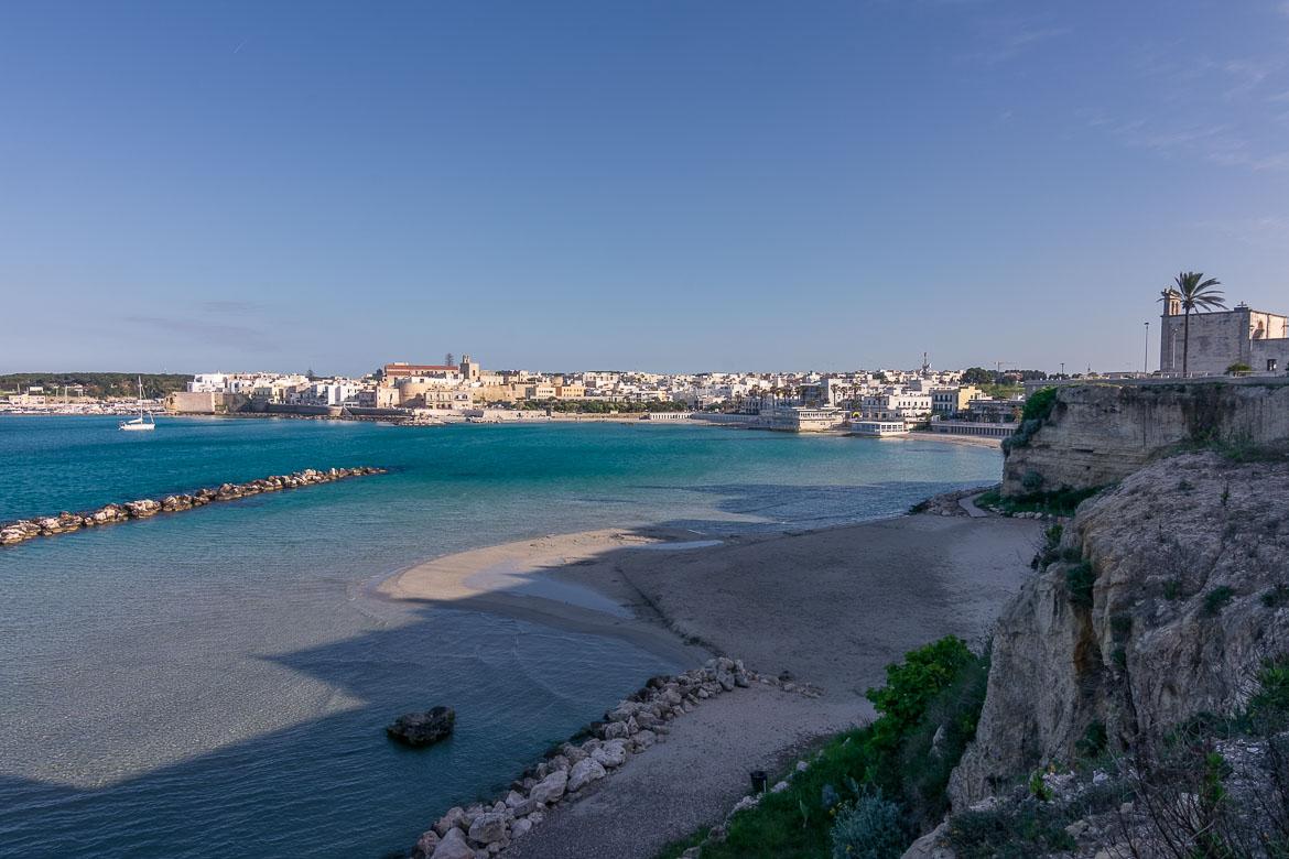 This is a photo of the sandy beach in the heart of Otranto. The waters are shallow and crystal clear. In the background, Otranto shines bright white in the afternoon sun.